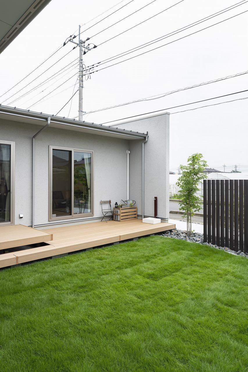 芝生の庭を囲むL字型の平屋の家